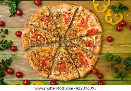 Cut into slices delicious fresh pizza with mushrooms and pepperoni on a green background. Top view . Pizza on the green table. - stock photo