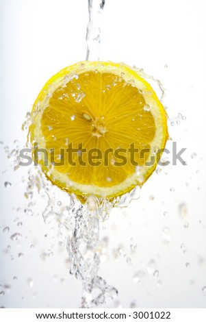 Cut lemon suspended in mid-air with water splashing around it