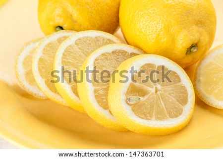 cut lemons on yellow porcelain plate