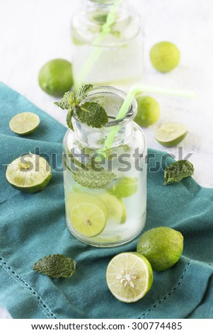 Cut lime and lime water with soda in vintage glass with straw. Refreshing summer party table top shot. - stock photo