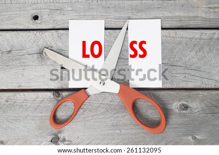 Cut loss concept against a wooden background - stock photo