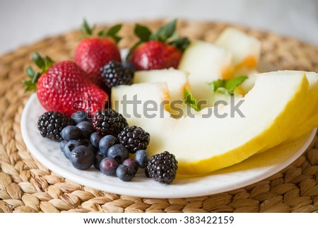 Cut melon and berries. Fruit salad of strawberries, blueberries, melon, mint and blackberries. Diet salad on the white plate - breakfast, weight loss concept. closeup. Healthy snack. - stock photo