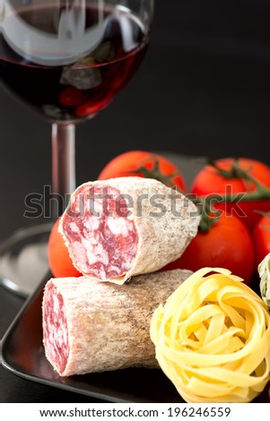 Cut of salami on plate with tomatoes and red wine - stock photo