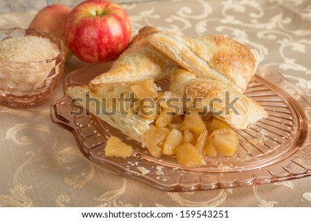 cut open apple turnover on and antique plate with apples and raw sugar - stock photo