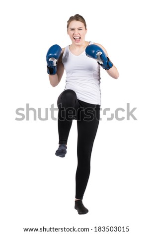 Cut out image of a young kickboxing women with blue boxing gloves who is performing a kick forward