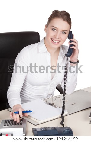 Cut out image of a young smiling woman who is phoning at the desk in front of her documents while using the desk calculator - stock photo