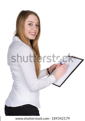 Cut out image of a young smiling woman who is writing at a clipboard while looking to the camera. - stock photo