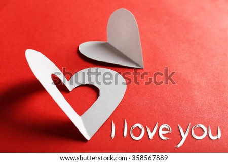 Cut out white paper hearts on red background - stock photo