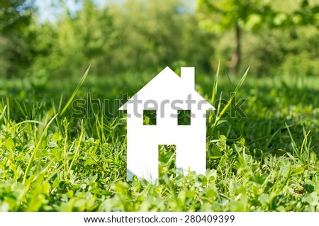 Cut out white paper house built on grass - stock photo