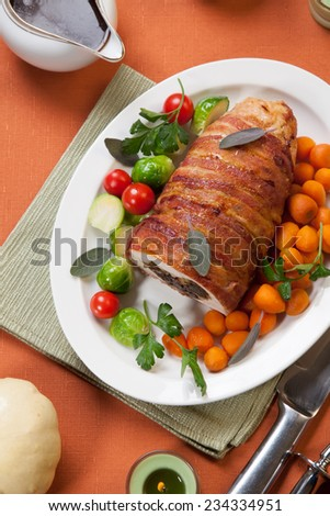 Cut piece of delicious bacon-wrapped turkey breast roulade stuffed with prunes and almond. Garnished with Brussels sprouts, tomatoes, and Parisian carrots.  - stock photo