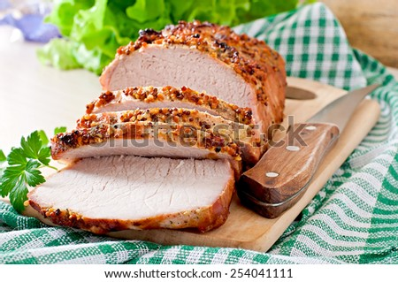 Cut pieces of baked meat on the table - stock photo