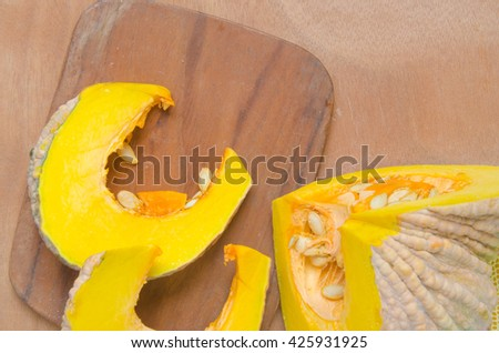 Cut pumpkin rests on a wooden cutting board Pumpkin is rich in plant nutrients have numerous health benefits. Can made a savory and sweet dishes. As well as a symbol of Halloween as well natural light