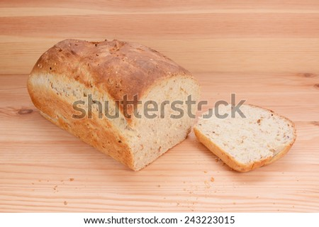 Cut slice from a freshly baked loaf of oat and linseed bread on a kitchen table - stock photo