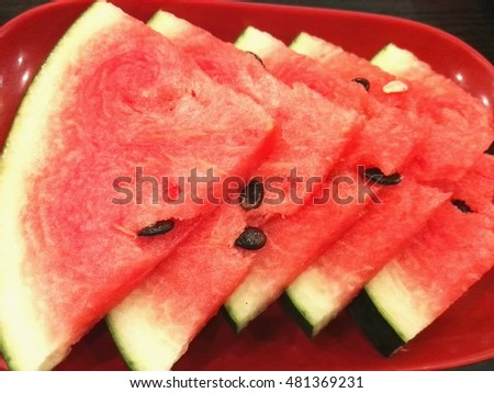 cut slices of watermelon on a wooden table and round lime, pear, grapes and leaves