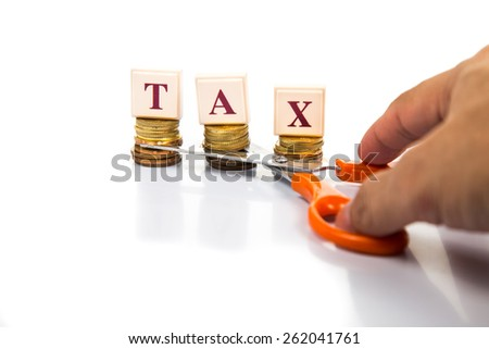 Cut taxes concept with coins, words and scissors - stock photo