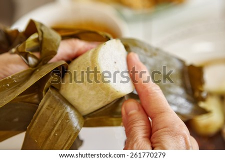 "Cut the steamed rice cake (""lontong"" in Indonesian) wrapped in banana leaf - stock photo"