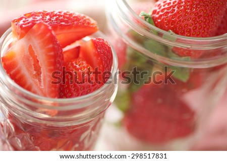 Cut up berries in glass canning jars - stock photo