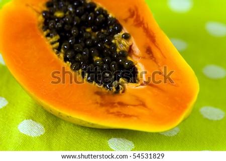 Cut up papaya fruit on green background - stock photo