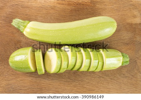 Cut vegetable marrows (zucchini) isolated on wooden background - stock photo