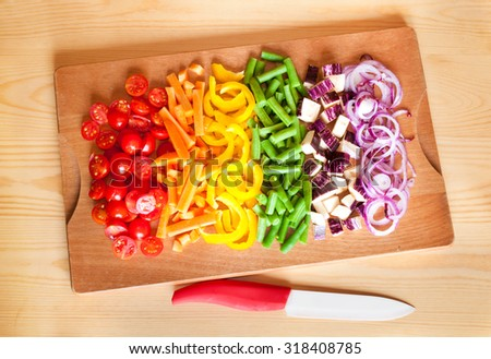 Cut vegetables of rainbow colors on wooden cutting board - stock photo