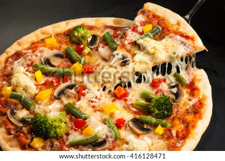 cut vegetarian pizza on a dark background with mushrooms, cheese and sweet pepper - stock photo