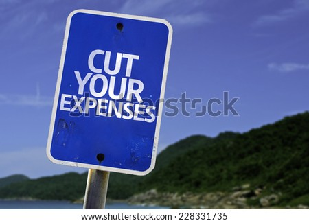 Cut Your Expenses sign with a beach on background - stock photo