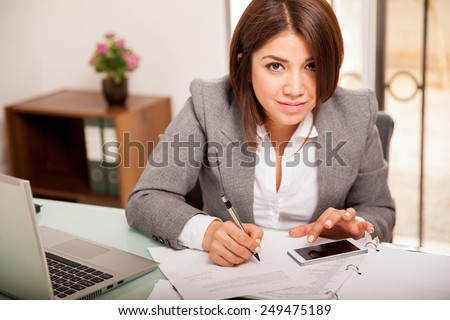 Cute accountant using her smart phone to do some calculations at work - stock photo