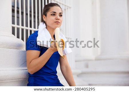 Cute active brunette relaxing after a long workout in the city and eating a banana - stock photo