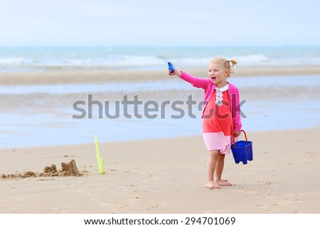 Cute active child wearing pink dress playing and dancing on wide sandy beach. Happy little girl enjoying summer holidays on a sunny day. Family with young kids on vacation at the North Sea coast.
