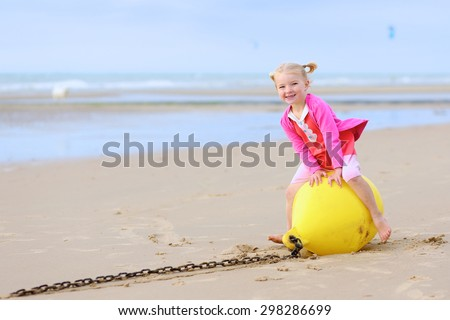Cute active child wearing pink dress playing on wide sandy beach. Happy little girl enjoying summer holidays on a sunny day. Family with young kids on vacation at the North Sea coast. - stock photo