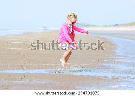 Cute active child wearing pink sunglasses playing and jumping on wide sandy beach. Happy little girl enjoying summer holidays on a sunny day. Family with young kids on vacation at the North Sea coast. - stock photo