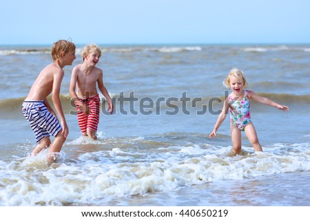 Cute active children playing and jumping in the sea. Happy siblings or friends enjoying summer holidays on a sunny day. Family with young kids on vacation at the North Sea coast. - stock photo