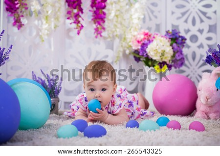 cute adorable baby girl sitting with spring flowers and easter decoration eggs colorful background