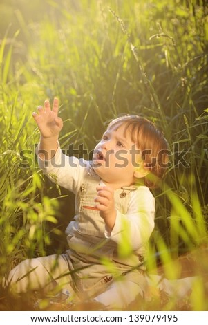 Cute adorable baby kid sitting in beautiful green grass - stock photo