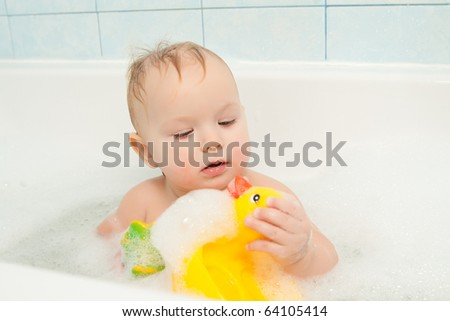 cute adorable baby play with toy sitting in foam bath