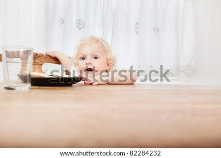 Cute adorable baby reaching for food on table - stock photo