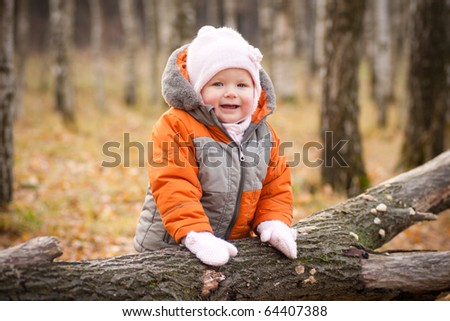 cute adorable baby smile and stay near fallen tree - stock photo