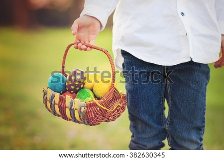 Cute adorable boy, gathering colorful easter eggs in a spring blooming cherry tree garden, smiling at the camera - stock photo