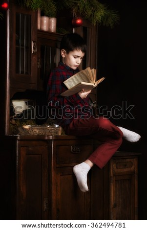 Cute adorable boy reading a book at christmas time. Cute adorable boy reading a book in front of the christmas tree, christmas time. - stock photo