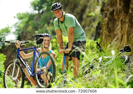Cute adorable couple smile and are happy with mountain bike outdoors - stock photo