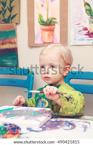 Cute adorable little baby boy girl toddler sitting in art studio indoors and drawing painting with brushes, pencils, pastel. Early child development concept