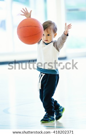 Cute adorable little small white Caucasian child toddler boy playing with ball in gym, having fun, healthy lifestyle childhood concept - stock photo
