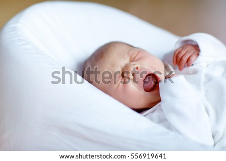 Cute adorable newborn baby crying in white bed. New born child, little girl laying in bed. Family, new life, childhood, beginning concept.
