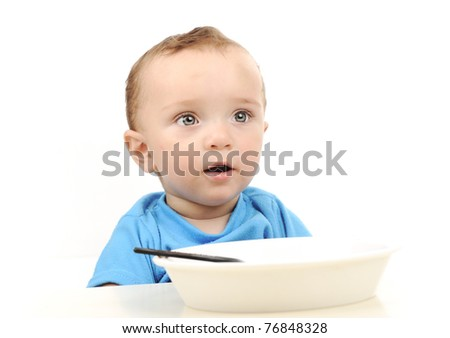 Cute adorable one year old baby with green eyes eating on table, spoon and plate