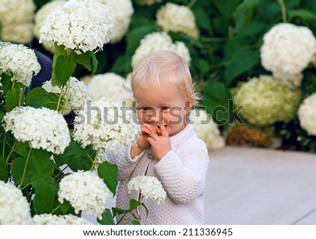 Cute adorable smiling baby child standing among flowers, lifestyle, happy childhood concept - stock photo