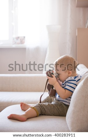 Cute adorable toddler boy sitting on the sofa in the living room and playing with vintage photo camera. Child taking picture. Future photographer.  - stock photo