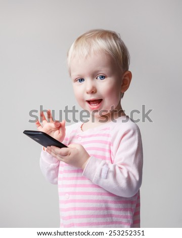 Cute adorable white Caucasian blond baby playing with mobile cell phone, chatting, with funny expression on her face, new technology concept, light background - stock photo
