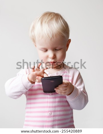 Cute adorable white Caucasian blond baby playing with mobile cell phone with funny expression on her face