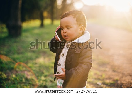 Cute African American Boy playing with Mobile Phone - stock photo