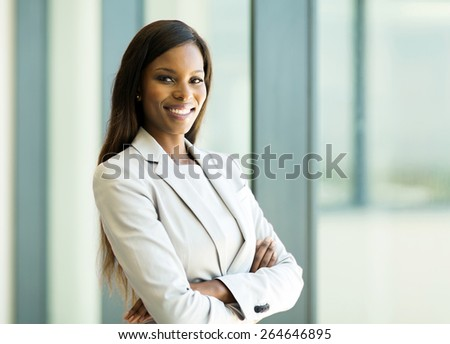 cute african american business woman with arms crossed in office - stock photo